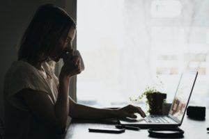 Woman sipping from a cup while sitting at a laptop on a desk working from home.